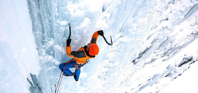 man scaling the side of a glacier