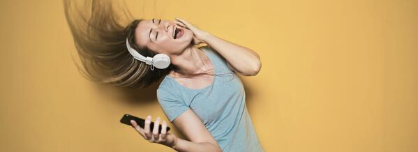 woman with headset holding a phone, listening and dancing to music on a yellow background