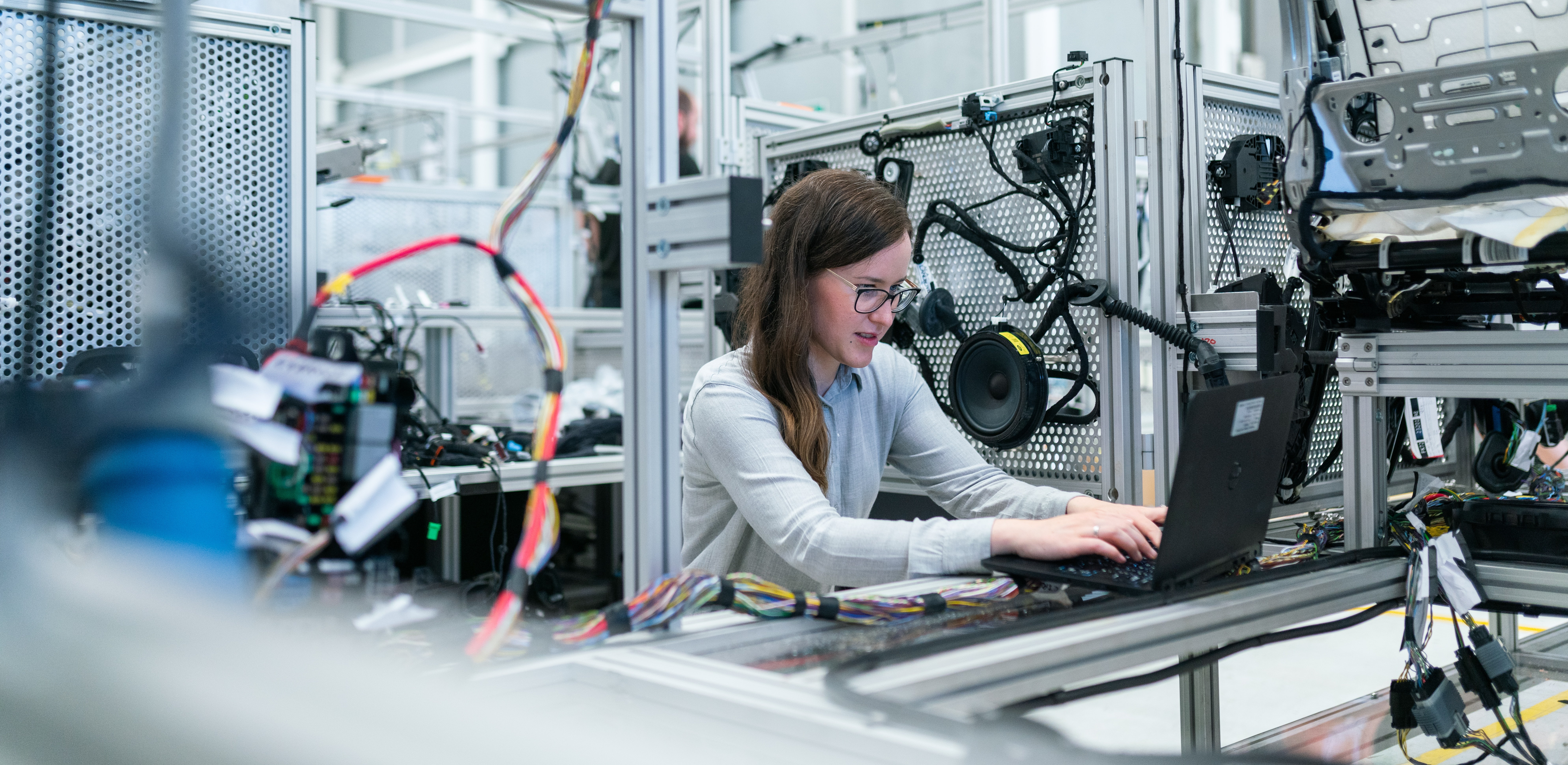 woman working on a laptop in an engineering manufacturing environment