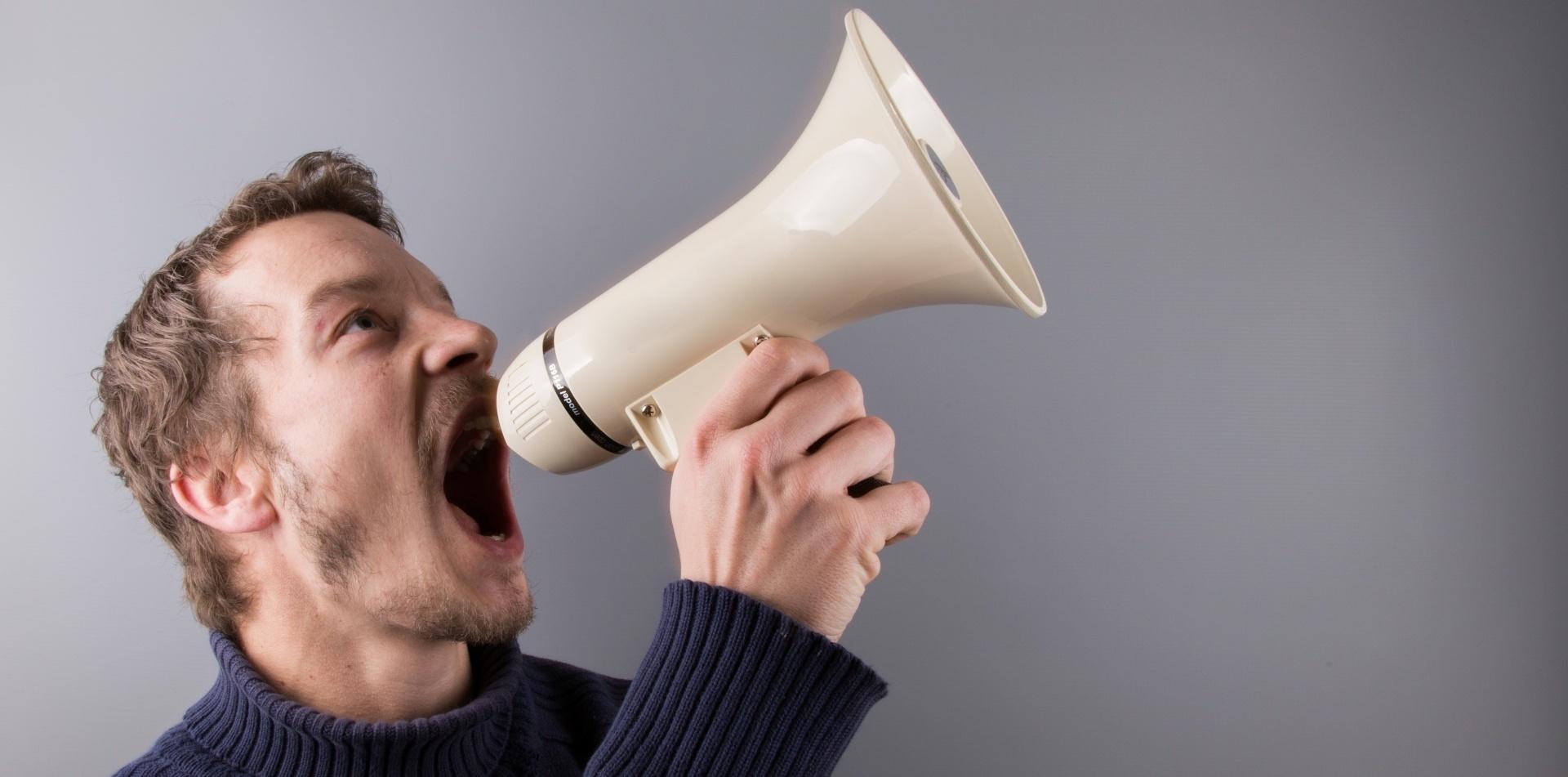 man screaming in megaphone