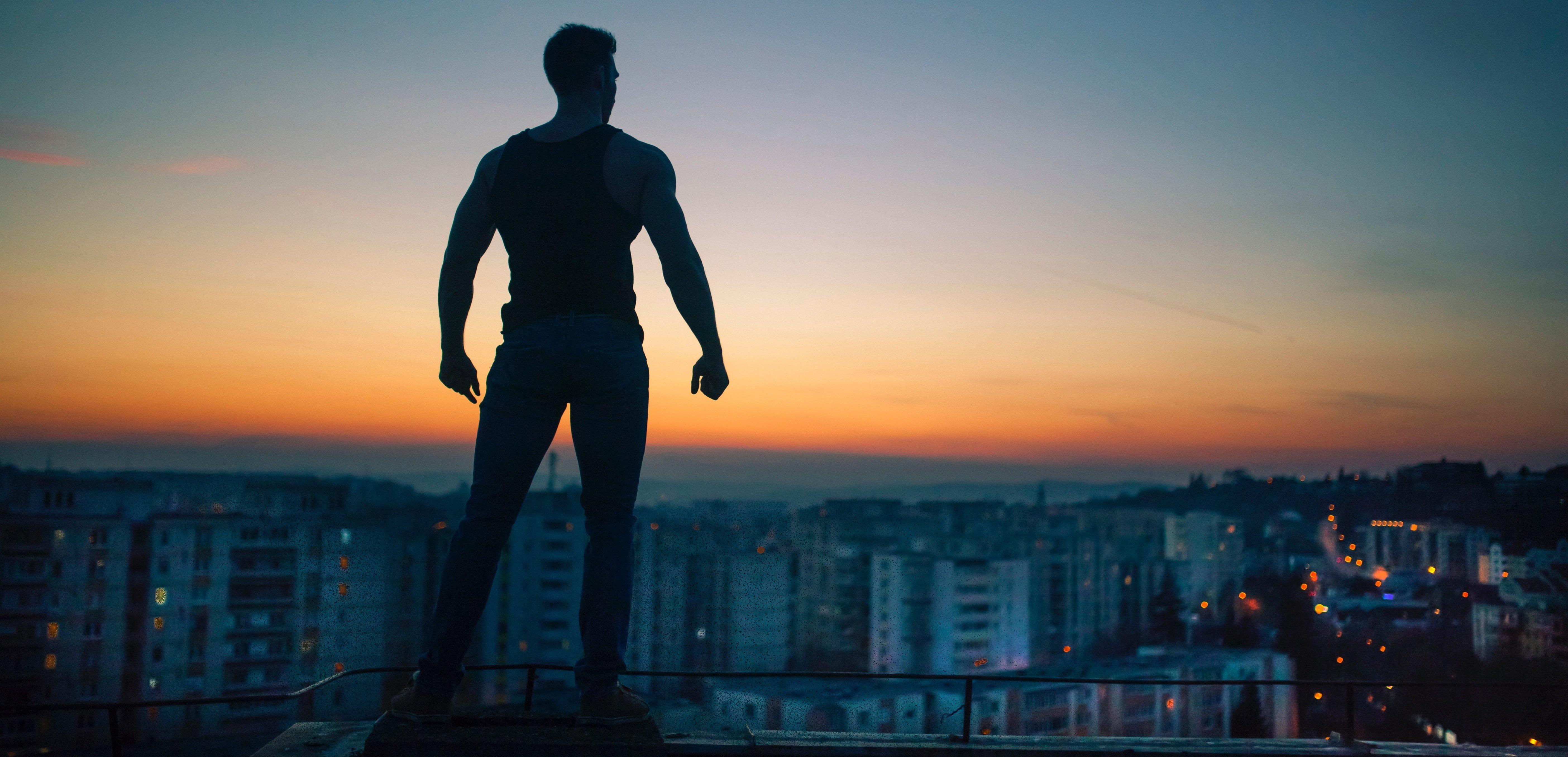 superhero overlooking a city at sunset